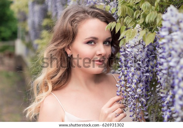 Wisteria. Portrait of a young beautiful woman near lilac flowers. Warm spring.