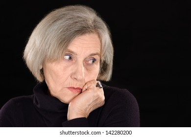 wistful senior woman thinking on a black background
