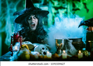 Witch with awfully face in creepy smoky green surroundings full of cobweb is reading recipe of magic drink. Halloween concept.