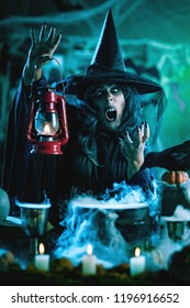 Witch with awfully face and lantern in her hand in creepy foggy surroundings sends evil. Halloween concept.