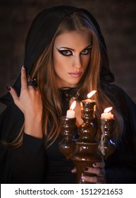 Witch in a black cloak. Sorceress with candles. Fairy girl halloween