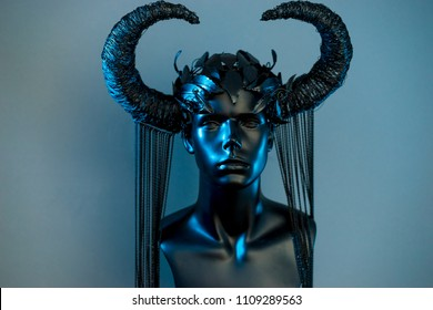 Witch. Black dress with helmet of big dark horns. pieces of metal and corset of rhinestones and lace