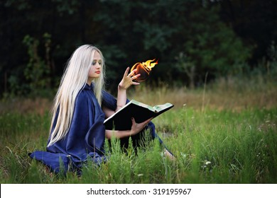 The witch with a book in the meadow practice witchcraft