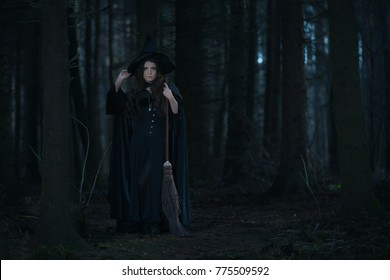 Witch with a broom in the forest