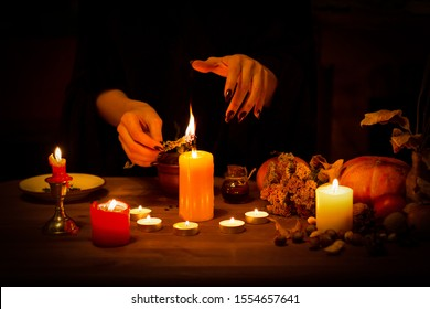 Witch burns a herb on the altar in the dark. Female hands with sharp black nails do magic among candles, pumpkin, nuts, dry leaves, selected focus, low key.