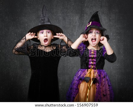 witch children scream and shout halloween costumes on two girls