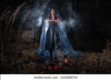 Witch conjures in t forest in the dark, a woman in a witch costume