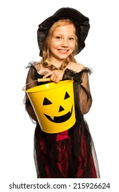 In witch costume holding Halloween bucket