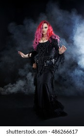 Witch creates magic. Attractive woman with red hair in witches costume