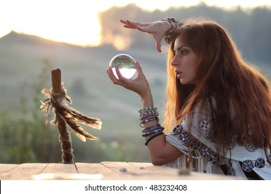 witch with crystal ball at sunset