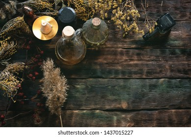 Witch doctor concept. Witchcraft background with copy space. Dried herbs and liquids in a bottles on a brown wooden table.