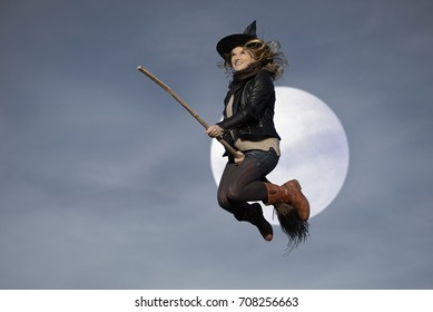 Witch flying riding on broom at full moon