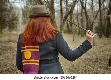 A witch girl with a magic wand in her hand, wearing glasses, a coat, a hat and a scarf, with a vintage bag, pronounces a spell. Back view