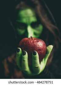 Witch green hand holding a rotten red apple. Shallow depth of field.