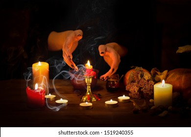 Witch guessing on wax on the altar in the dark. Female hands with sharp black nails making passes above candles, pumpkin, nuts, dry leaves, magic herbs, selected focus, low key. Halloween, Yule