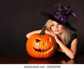 Witch with Halloween pumpkin. Beautiful blonde girl