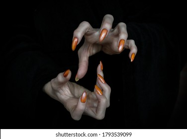 Witch hands with sharp nails and long pale fingers in the dark, low key, selected focus. Halloween, witchcraft, magic, evil, creepy and monster concept.