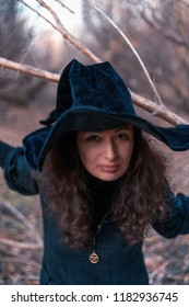 Witch in hat in woodland scary toned image
