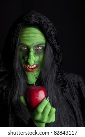 Witch and her poisonous apple, black background.