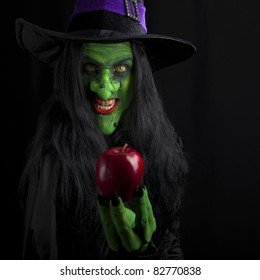 Witch and her poisonous red apple, black background.