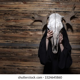 Witch holding animal skull skull standing on wood background. Halloween, black magic mystical ritual concept.
