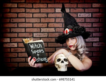 Witch leaning on skull while reading her spell & potion book.