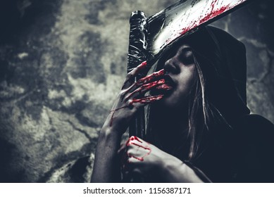 Witch licking blood on fingers. Female demon angel in black clothes and hood on grunge wall background. Halloween day and Mystery concept. Fantasy of magic theme. Afterlife and Death concept.