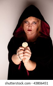 Witch in long black robe standing in corner with Talisman