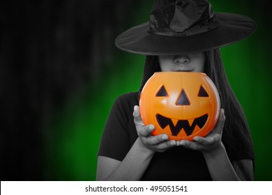 Witch magic holloween woman holding pumpkin toy.