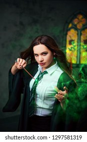 Witch with a magic wand. A young student of the magic school conjures. The girl conjures green magic in the dark hall of the castle.