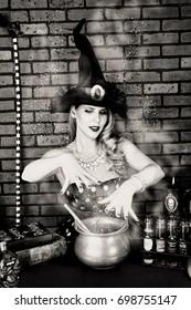 Witch making a potion in a cauldron.  Black & White.