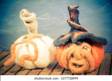 Witch and pumpkin face carded wool felted with needle DIY house decorating for Halloween Thanksgiving Day Saints dead Dia de muertos vintage on wood closeup