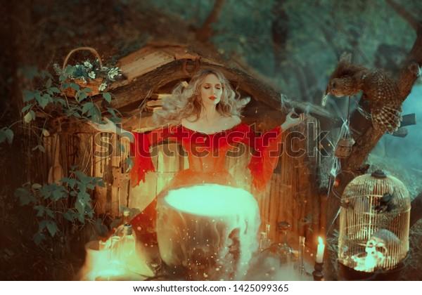 Hexe in einem roten Kleid mit kahlen Schultern der Barockzeit, bereitet ein Gift. Die Zauberin ruft die Kräfte der Magie auf, die Mentalität erfüllt ihren Tränen. mit einem Wind fliegt ihr Haar weg