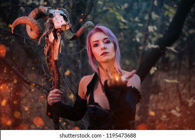 A witch with a staff from the skull of a ram conjures in the forest. A girl in a black dress and purple hair. Image for halloween