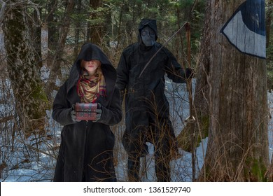 Witch woman in hooded mantle holds magic ancient casket box, man in death costume with scythe stands behind in dark forest