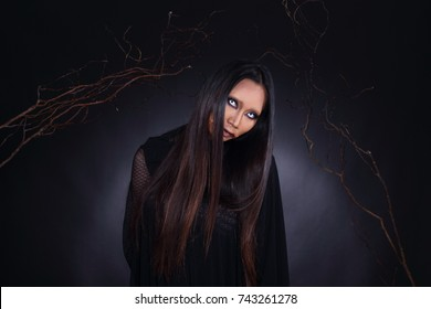 Witchcraft Asian woman in scary Witch ghost story look, white eyes cut mouth blood wound black long hair, studio lighting dark background wood branch stick