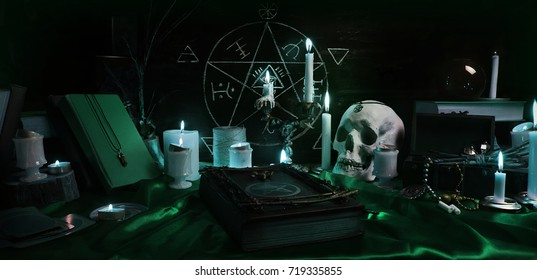 Witchcraft composition with burning candles, human skull, magic books, jewelry, tarot cards and pentagram symbol. Halloween and occult concept, black magic ritual.