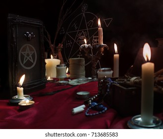 Witchcraft composition with burning candles, magic book, quill, jewelry, chalk and pentagram symbol. Halloween and occult concept, black magic ritual.
