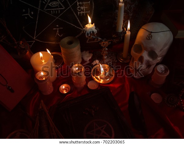 Witchcraft composition with human skull, burning candles, magic book, amulets and pentagram symbol. Halloween and occult concept, black magic ritual.