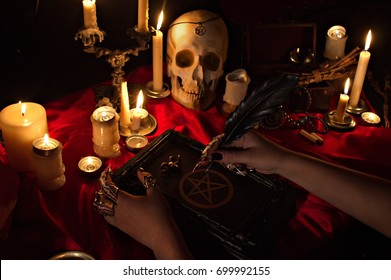Witchcraft composition with witch's hands holding a quill, satanic magic book with pentagram symbol, human skull and candles. Halloween and occult concept, black magic ritual.