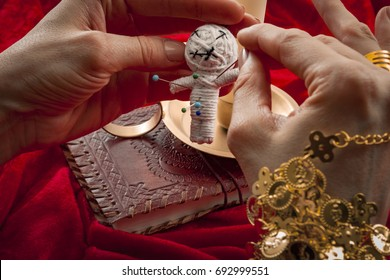 Witchcraft and how to place a jinx or put a spell on someone concept with a woman witch piercing a voodoo doll with needles to cause harm to her victim. Each needle represents a different curse