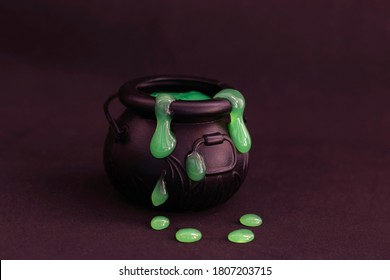 Witch's cauldron on a black background. Green slime flows out of the boiler. Witchcraft, halloween.