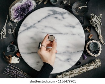 Witch's hand holding Smoky quartz above a marble white round tray. The place for witchcraft with magic things around. View from above.