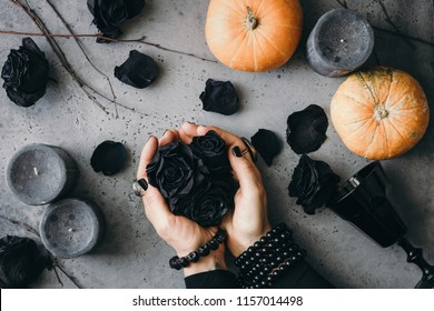 Witch's hands holding black roses over grey background surrounded black candles, small pumpkins, dried branches and vintage wineglass . Halloween concept, flat lay, top view.