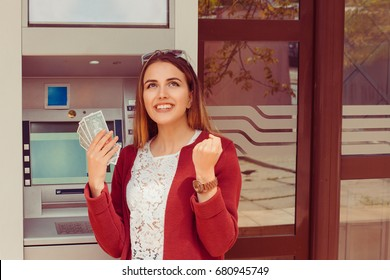 Withdraw.  ATM. Portrait happy smiling woman exults pumping fists ecstatic celebrates success holding cash dollar money bills banknotes isolated outside Atm background with copy space. Casual clothing