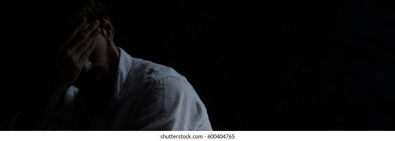Withdrawn broken down man with depression sitting alone