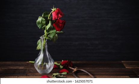 Withered rose on dark gray background and wooden table with fall petals and leaves, design concept of sad Valentine's day romance, broken up, copy,space.