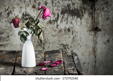 Withered roses in vase on old wooden