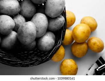 Within a wicker basket are several pounds of New Potatoes with peeler at side
