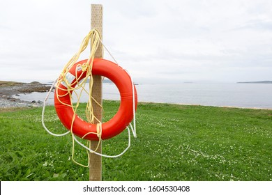 Witless Bay, NL / Canada - 30 July 2019: Orange life buoy at Witless Bay in Newfounland and Labrador, Canada. The safety device is designed for use by people in the water.